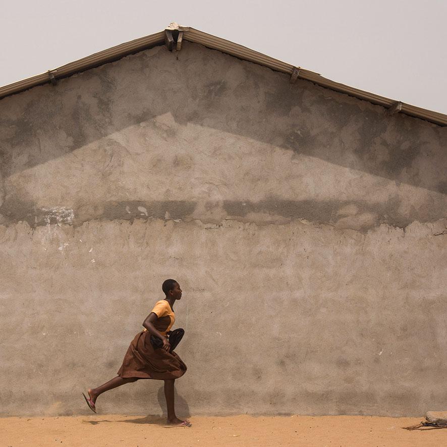 Ein Schulmädchen sucht Schutz vor den Wassermassen, die das Dorf überfluten.