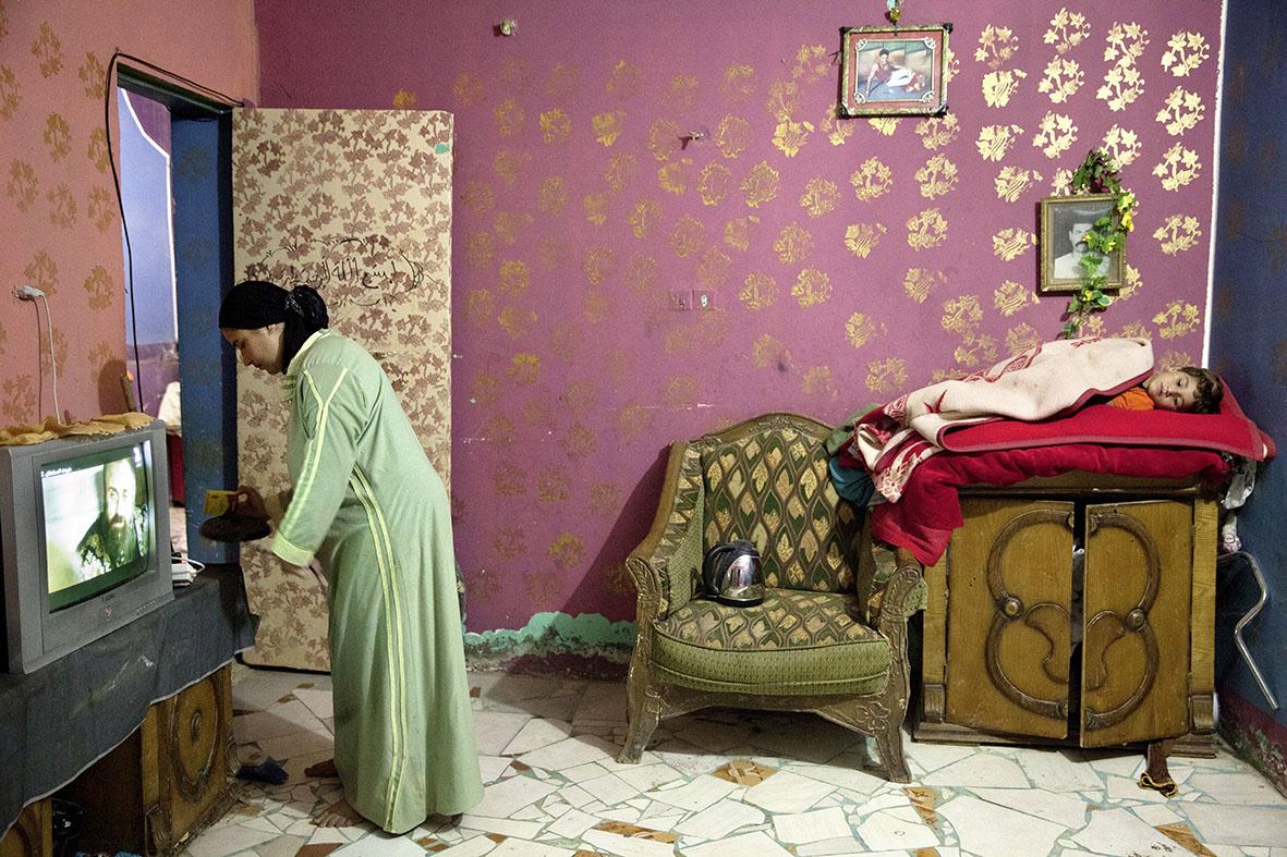 Ein Blick ins Wohnzimmer einer muslimischen Familie. Auf einer Kommode, gebettet auf Decken, döst ein Bub. Die Ablage ist sein ständiger Schlafplatz. Ausstrecken kann er sich nicht. Schon jetzt hängen seine Beinchen über den Schrank.