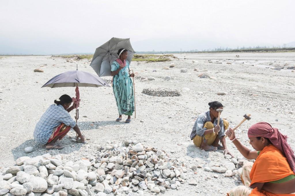 Bishmoni Tanti (links) zerschlägt am Ufer der Diana Steine. Seitdem die Teeplantage, auf der sie gearbeitet hat, geschlossen ist, kämpft sie ums Überleben.