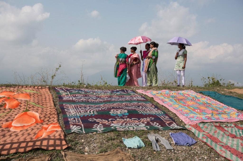 DorfbewohnerInnen trocknen an den Hängen des Flusses Diana ihre Tücher.
