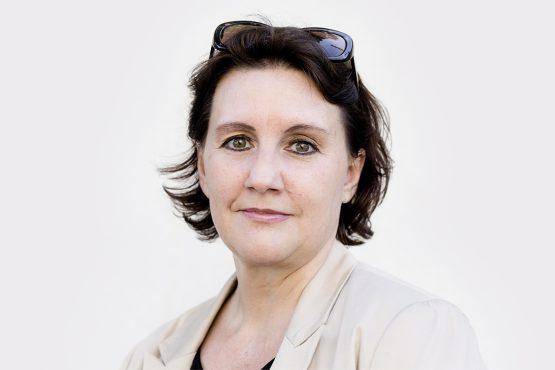 Porträt von Sabine Kogler vor heller Wand