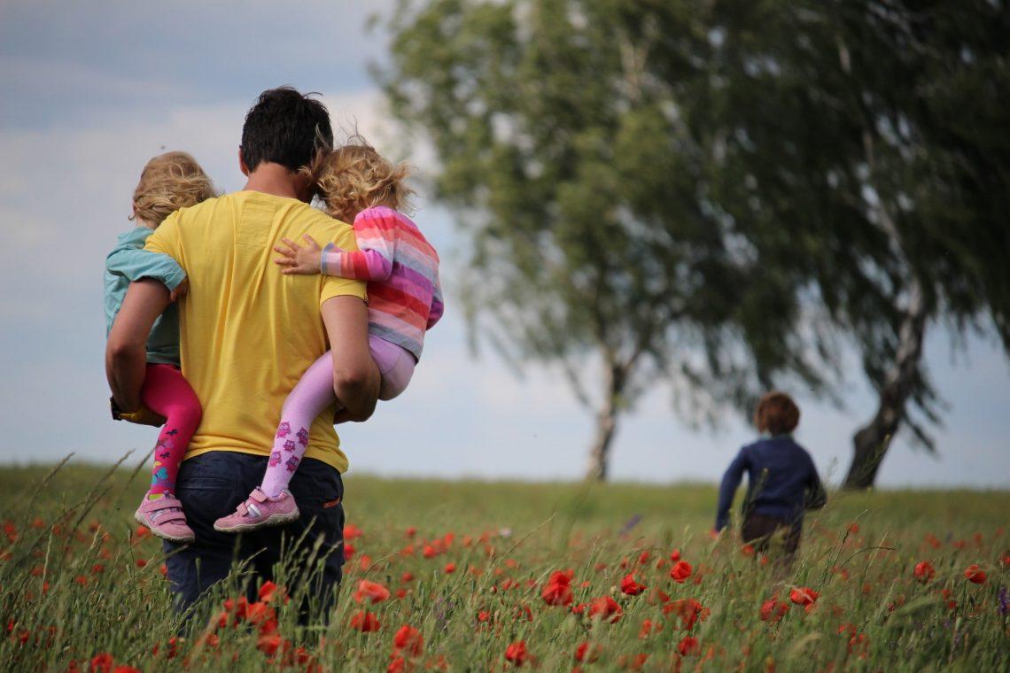 Vater mit Töchtern aufdem Arm